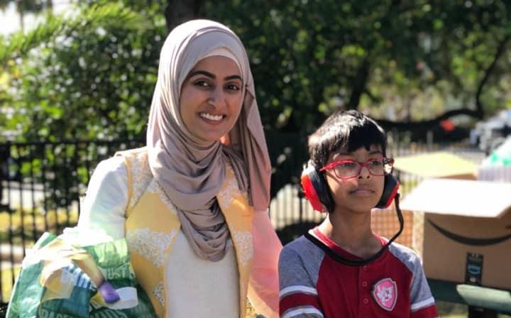 Certified Muhsen respite volunteer standing beside a boy with special needs wearing noise canceling headphones.