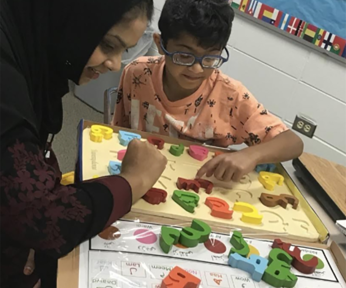 Boy with special needs working on Arabic letter board with a MUHSEN certified TA.