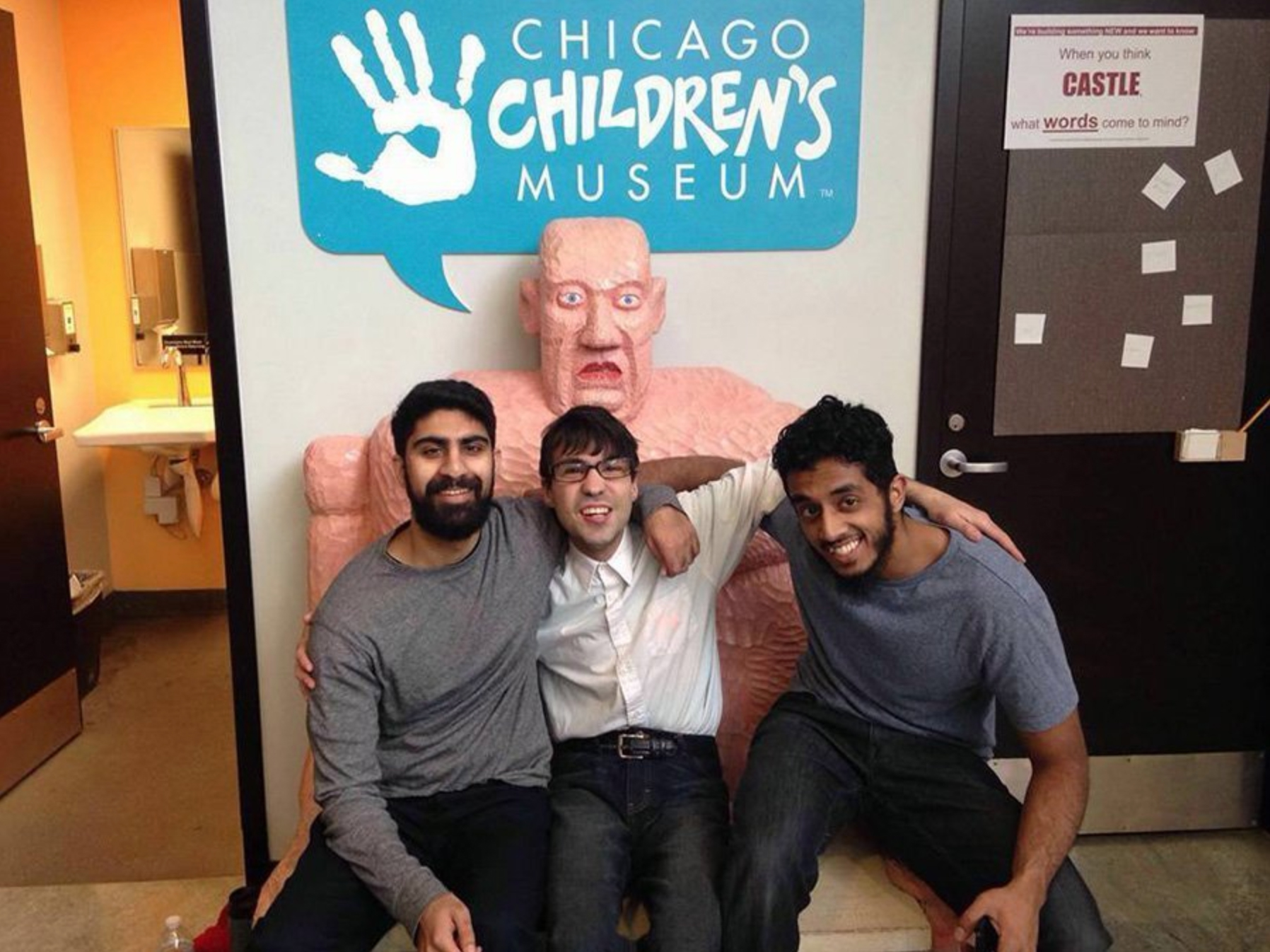 A young man with special needs sitting between two certified MUHSEN respite volunteers at Chicago Children's Museum.