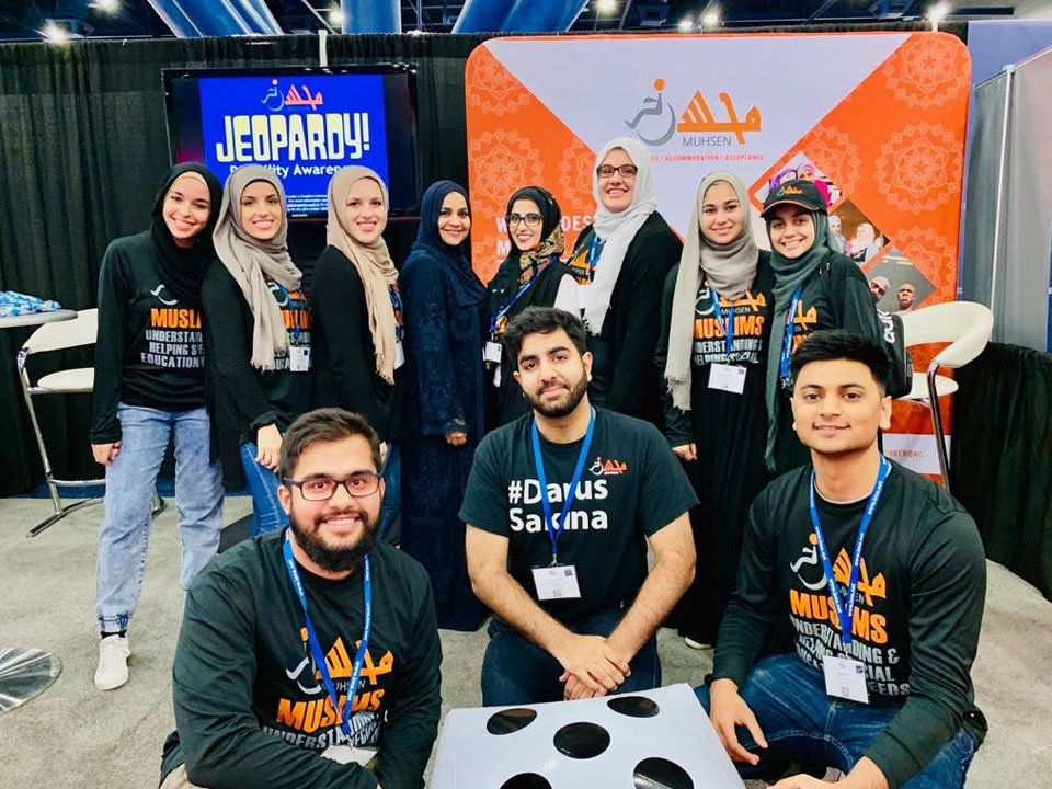 Joohi Tahir and 10 volunteers are posing in front of the MUHSEN booth during the ICNA convention.