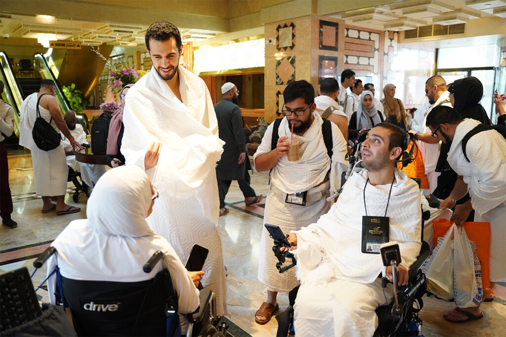 two muhsen volunteers and two people with special needs at muhsen umrah