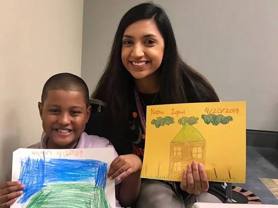 Certified Muhsen respite volunteer and a young boy with special needs are proudly showing their artwork.