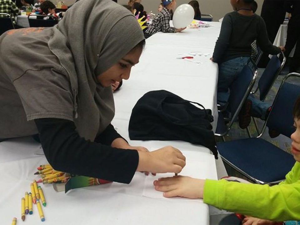 A child with special needs getting his hand traced by a certified Muhsen respite volunteer.