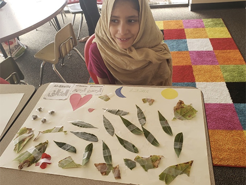 A girl with special needs sitting with her artwork of leaves displayed on her desk.