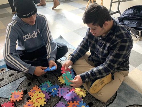 2 young men sitting and working on the Arabic alphabet puzzle.