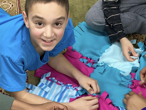 A boy with special needs working on a quilting pattern as he poses for the camera.