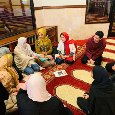 9 women and 1 men are sitting in a circle and participating in a professionally-led MUHSEN support group hosted at the masjid.