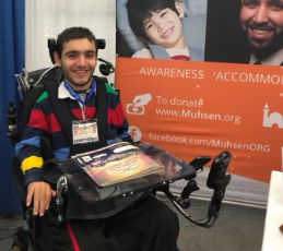 Boy sitting in a wheel chair, smiling in front of a MUHSEN sign