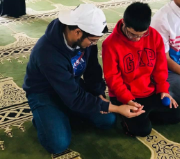 Boy helping a boy with special needs do dhikr